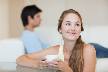 Woman drinking coffee while her fiance is sitting on a couch in their living room photo