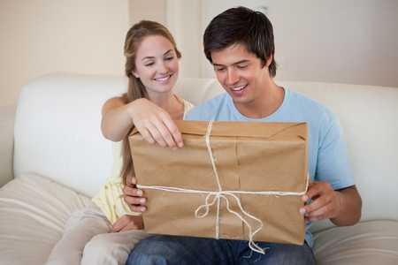Couple opening a package in their living room photo