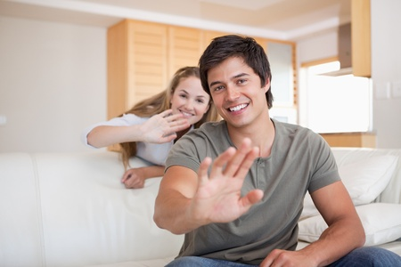 Couple waving at the camera in their living room photo
