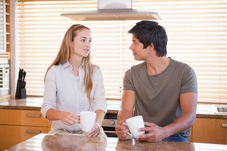 two people talking: Pares que tienen una taza de caf� en su cocina