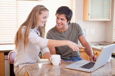 Smiling couple having coffee while using a notebook in their kitchen photo