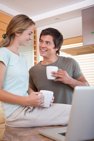 Portrait of a young couple having coffee while using a notebook in their kitchen photo