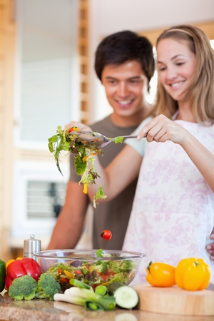 Portrait of a charming couple making a salad in their kitchen photo