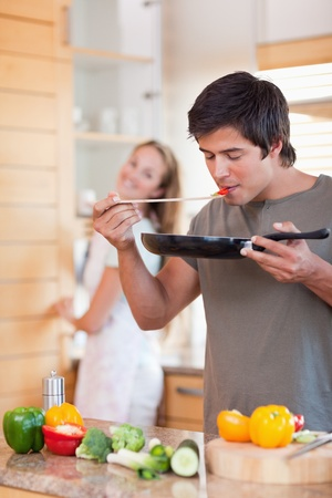 Portrait of a man cooking while his girlfriend is washing the dishes in their kitchen photo