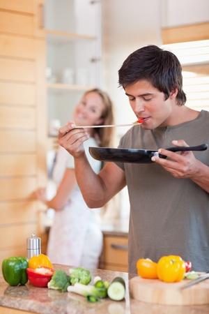 hombre cocinando: Retrato de un hombre que cocina mientras su novia se est� lavando los platos en la cocina Foto de archivo
