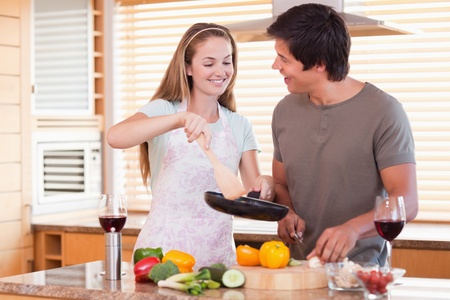 Couple cooking dinner in their kitchen photo