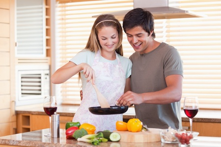 vegetables young couple: Couple cooking dinner while drinking red wine in their kitchen