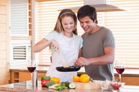 aceite de cocina: Pareja preparando la cena, mientras que beber vino tinto en su cocina Foto de archivo