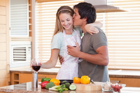 romantic: Lovely couple drinking red wine while kissing in their kitchen Stock Photo