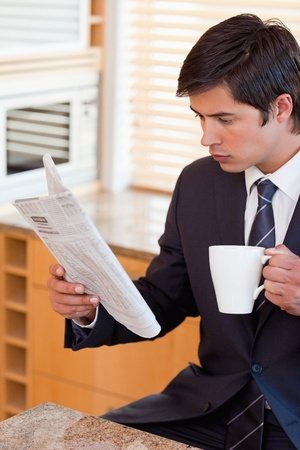 Portrait of a businessman drinking tea while reading the news in his kitchen photo