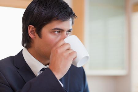 Close up of a businessman drinking tea in his kitchen photo