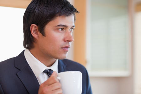 Close up of a handsome businessman drinking tea in his kitchen photo