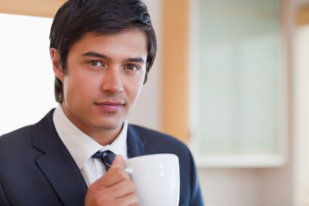 Close up of a handsome businessman drinking coffee in his kitchen photo