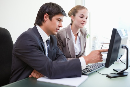 Good looking business people working with a computer in an office photo