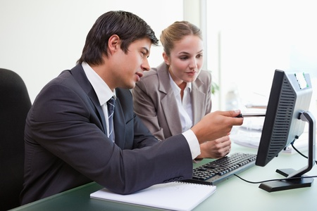 Focused business team working with a computer in an office photo