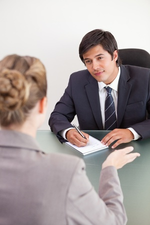 applicant: Portrait of a smiling manager interviewing a female applicant in an office