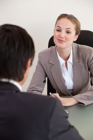 Portrait of a manager interviewing a male applicant in her office photo