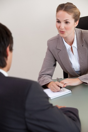 Portrait of a serious manager interviewing a male applicant in her office photo