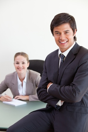 Portrait of a businessman posing while his colleague is working in an office photo