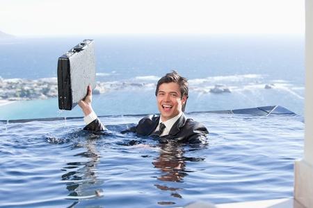 ahogandose: Hombre de negocios con un malet�n en una piscina Foto de archivo