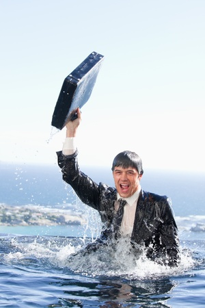 Portrait of a young businessman going out of the water with a briefcase in a swimming pool photo