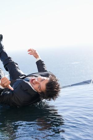 hombre cayendo: Retrato de un hombre de negocios cae en el agua con el pulgar hacia arriba Foto de archivo