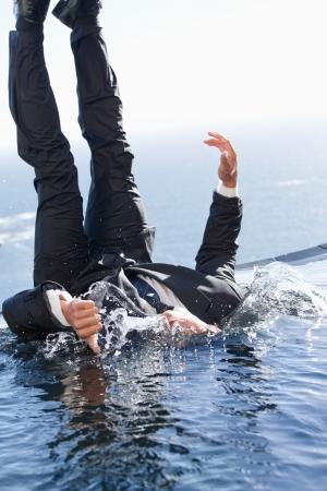 ahogandose: Retrato de un hombre de negocios alegre caer en el agua con el dedo pulgar hacia arriba