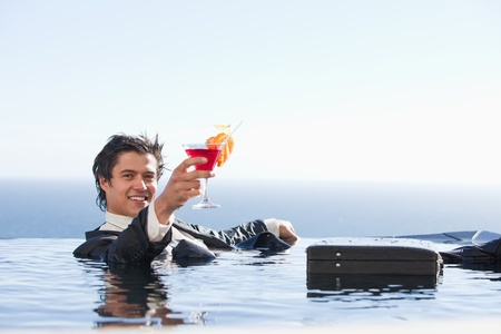 Cheerful businessman relaxing in a swimming pool with a cocktail in a suit photo