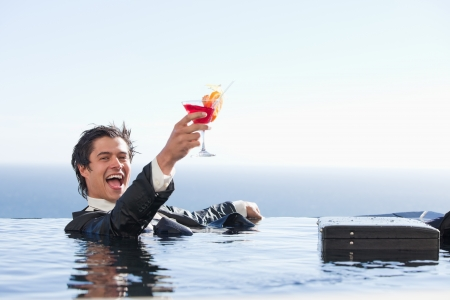 Delighted businessman relaxing in a swimming pool with a cocktail in a suit photo