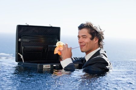 Businessman drinking a cocktail in a swimming pool photo