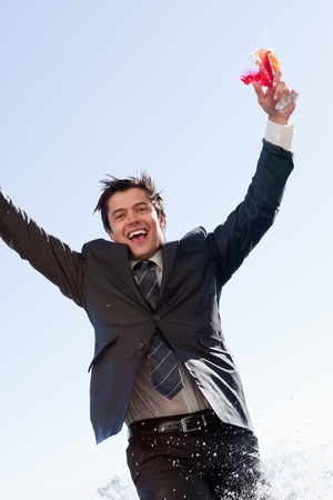 Portrait of a businessman jumping in a swimming pool with a cocktail photo