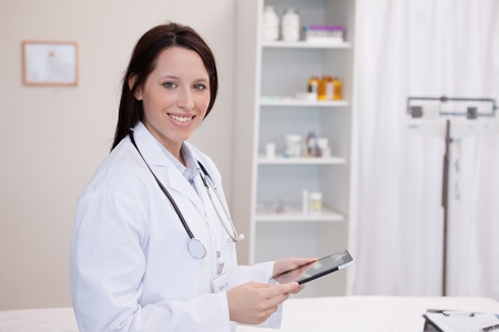 Smiling doctor using a tablet computer in a hospital Stock Photo - 11685964