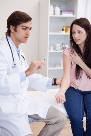 Male doctor about to give an injection to patient photo