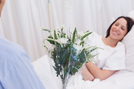 healthcare visitor: Flowers are brought to female patient