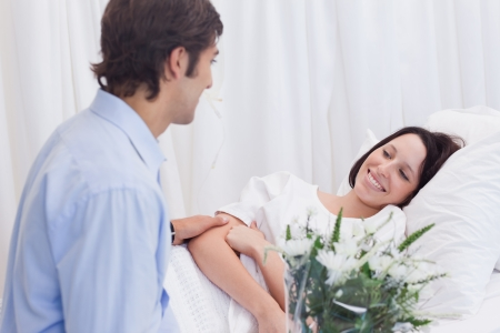 Young man visiting his girlfriend in the hospital photo