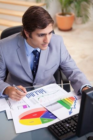 selling stocks: Young businessman analyzing statistics at his desk