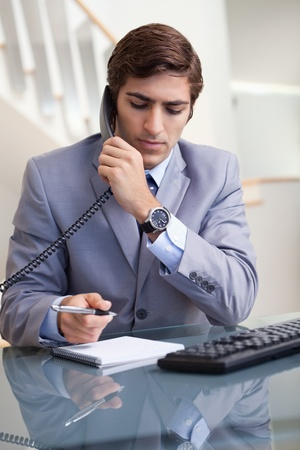 Young businessman taking notes while on the phone Stock Photo - 11681469