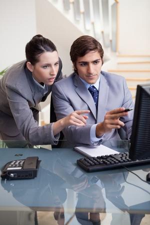 J�venes cu�l de negocios que muestra en su pantalla a sus colegas photo