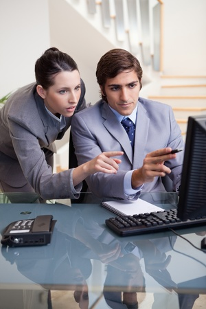explaining: Young businessman showing whats on his screen to his colleagues