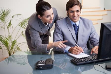 Hombre de negocios joven que explica su colega lo que tiene que hacer photo