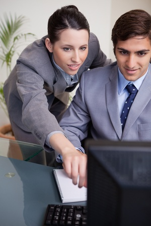 Young businesswoman explaining her colleague what his task is photo