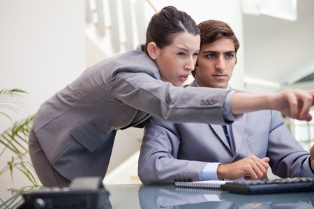Young businesswoman explaining computer program to colleague photo