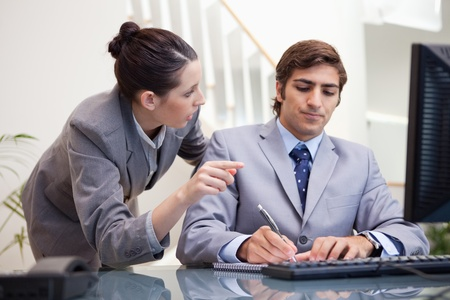 Young businessman taking notes while getting explanation by colleague photo