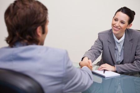 headhunting: Young businesswoman welcomes customer in her office Stock Photo