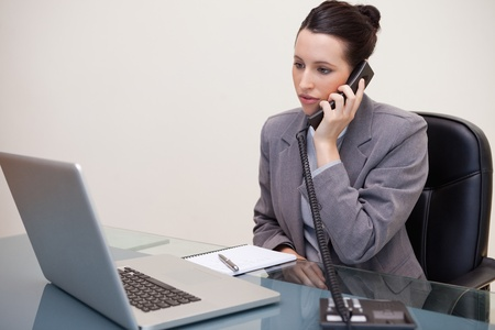 Young businesswoman sitting at her desk on the telephone photo