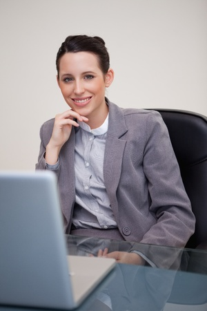 Smiling young businesswoman sitting in her office photo