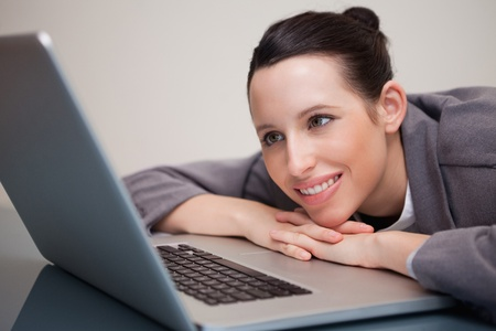 Smiling young businesswoman leaning against her laptop photo