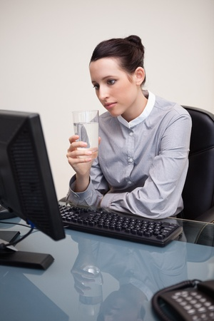 Young businesswoman at her desk with a glass of water Stock Photo - 11682791