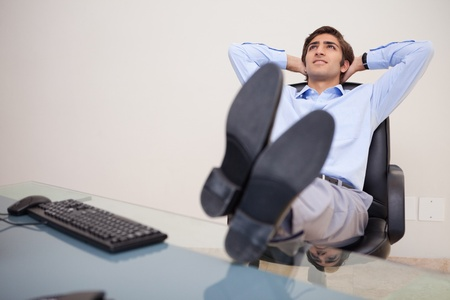 Young businessman leaning back in his chair photo