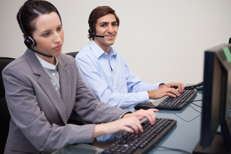 Side view of young call center agents working in their office photo